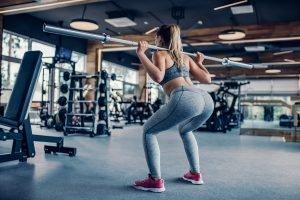 frau in fitness kleidung macht kniebeugen mit langhantel