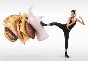 gesunde frau tritt burger pizza und milkshake weg symbolbild heilfasten