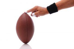 kleiner finger mit tapeverband und football