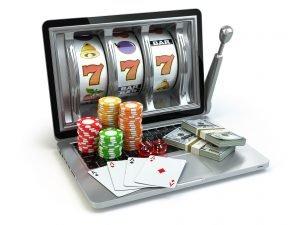laptop mit slotgame casino chips geld und karten