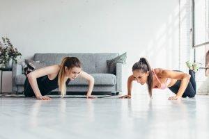 Frauen trainieren zusammen Liegestütze