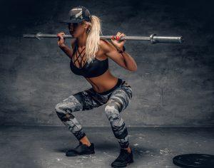 Frau bei Kniebeugen mit Langhantel ohne Gewicht
