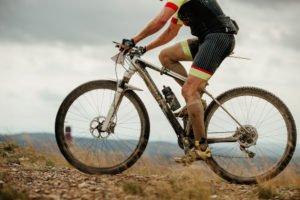 Mann fährt mit Mountainbike bergauf durch Matsch