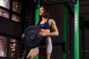 Frau macht Workout mit Hantelscheibe