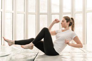Frau trainiert Radl-Crunches Zuhause