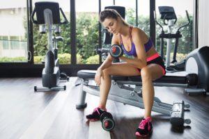 Frau trainiert im Fitnessstudio mit Kurzhanteln
