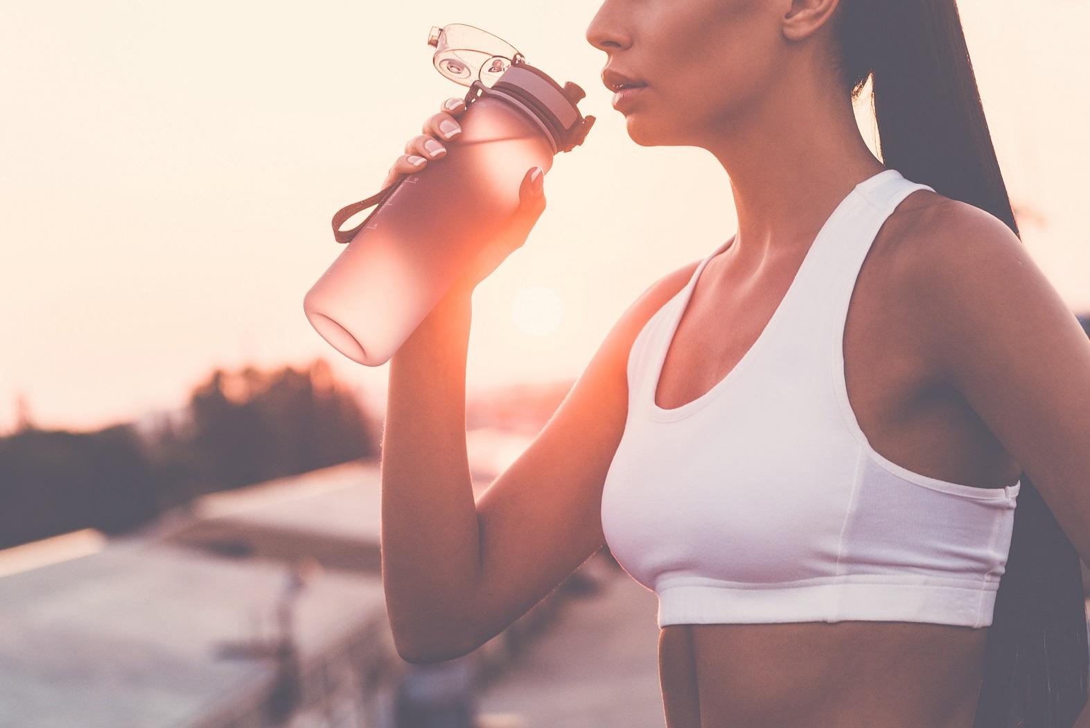 frau trinkt beim sport auf wasserflasche