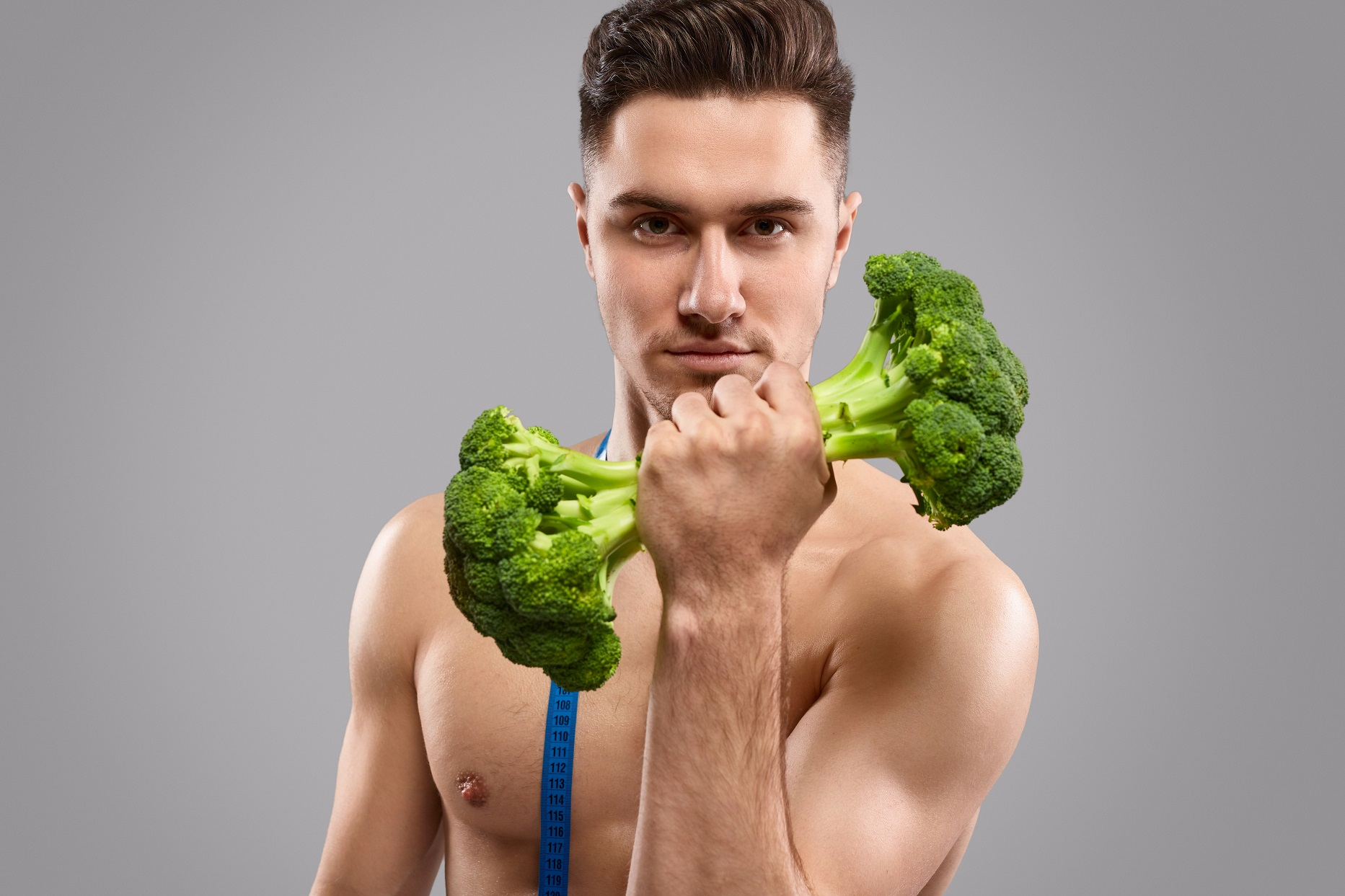 man beim sport mit brokkoli als hantel