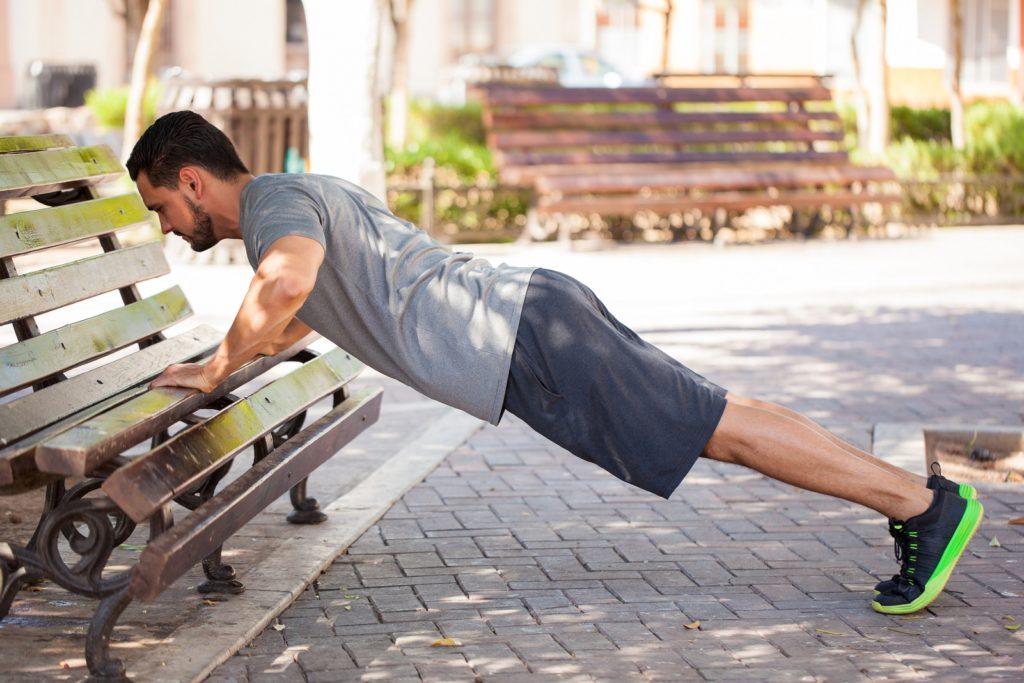 Mann macht Outdoor Fitness auf Parkbank