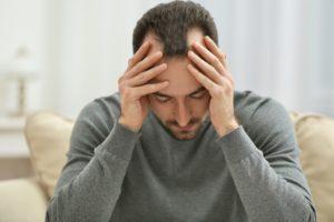 Mann mit Kopfschmerzen in depressiver Stimmung