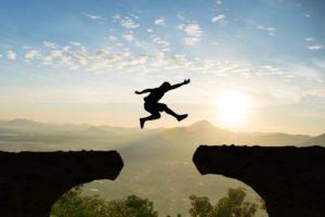 Mann springt über Schlucht