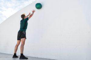 Mann wirft Medizinball gegen Wand