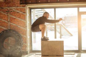 Plymetrisches Training: Mann springt auf Plyo-Box