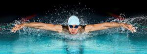 Fitness und Muskeln aufbauen durch Schwimmen: Mann beim Delphinschwimmen