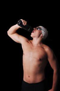 Schwimmer trinkt Wasser