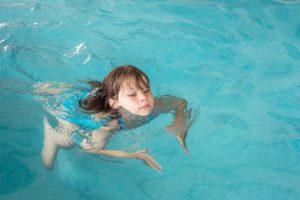 ein kleines maedchen beim schwimmen lernen