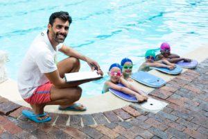 kinder lernen in einem schwimmkurs gemeinsam schwimmen